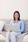 Smiling woman on the sofa surfing the internet Royalty Free Stock Photography
