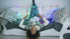 Smiling woman on sofa with twinkle lights. Playful young model in casual clothing lying upside down on sofa at home all covered with blinking lights of Christmas stock footage