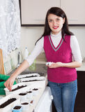 Smiling woman sowing seeds in pots at table Stock Photos