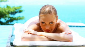Smiling woman on spa bed next to swimming pool Stock Photos