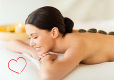 Smiling woman in spa salon with hot stones Royalty Free Stock Photo