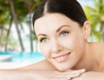 Smiling woman in spa salon. Spa, resort and vacation concept - smiling woman in spa salon lying on the massage desk stock image