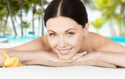 Smiling woman in spa salon. Spa, vacation and resort concept - smiling woman in spa salon lying on the massage desk stock images