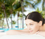 Smiling woman in spa salon. Spa, vacation and resort concept - smiling woman in spa salon lying on the massage desk stock photo