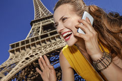 Smiling woman speaking on a cell phone and hand waving in Paris Stock Photo