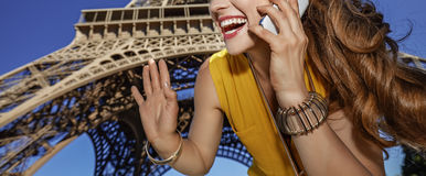 Smiling woman speaking on a cell phone and hand waving in Paris Stock Photos