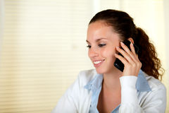 Smiling woman speaking on cellphone Stock Images