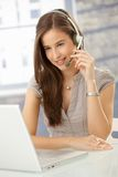 Smiling woman speaking on headset. Using laptop computer, looking at screen royalty free stock photography