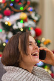 Smiling woman speaking mobile near Christmas tree Stock Photography