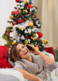 Smiling woman speaking mobile near Christmas tree Royalty Free Stock Photography