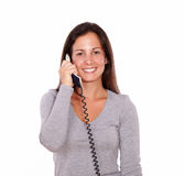 Smiling woman speaking on phone looking at you Stock Photo