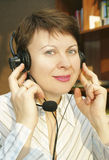 Smiling woman speaks by headphone Royalty Free Stock Images