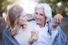 Smiling woman spending picnic with retired mother in the park. Enjoying happy life. Charming satisfied young woman enjoying picnic and eating cupcake while Stock Photo