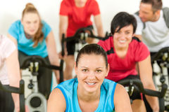 Smiling woman at spinning class fitness workout. Smiling women at spinning class fitness workout people exercise Royalty Free Stock Photo