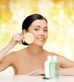 Smiling woman with sponge and cosmetic bottles Royalty Free Stock Photo