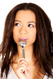 Smiling woman with spoon in her mouth. Royalty Free Stock Images
