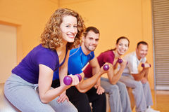 Smiling woman in sports group. Smiling women with dumbbells exercising in sports group in gym Stock Photo