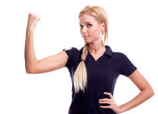 Smiling woman in sports wear showing her biceps. Young happy smiling woman in sports wear showing her biceps stock image