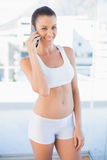 Smiling woman in sportswear calling Stock Photo