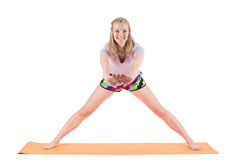Smiling woman in sportswear stretching back and legs on a mat Stock Images