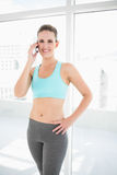 Smiling woman in sportswear talking on the phone one hand on hip Royalty Free Stock Image