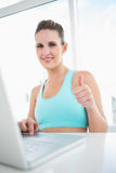 Smiling woman in sportswear using laptop giving thumbs up Royalty Free Stock Photos