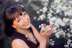 Smiling woman in a spring garden holding flower Stock Photos