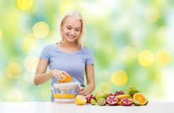 Smiling woman squeezing fruit juice Royalty Free Stock Photography