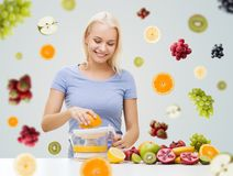 Smiling woman squeezing fruit juice at home Royalty Free Stock Images