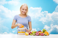 Smiling woman squeezing fruit juice over sky Royalty Free Stock Photography
