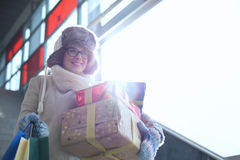 Smiling woman with stacked gifts and shopping standing by window during winter Stock Image