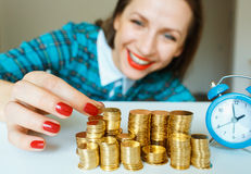 Smiling woman stacking gold coins into columns Royalty Free Stock Image