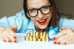 Smiling woman stacking gold coins into columns Stock Photo