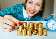 Smiling woman stacking gold coins into columns Royalty Free Stock Images