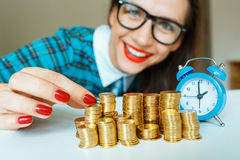 Smiling woman stacking gold coins into columns Royalty Free Stock Photography