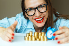 Smiling woman stacking gold coins into columns Stock Image