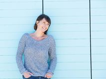 Smiling woman standing against blue background Royalty Free Stock Images