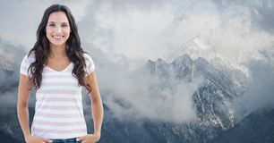 Smiling woman standing against mountains surrounded by fog. Digital composite of Smiling woman standing against mountains surrounded by fog Royalty Free Stock Photography