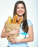 Smiling woman standing against white background with bread and m. Ilk. Isolated portrait Stock Photography