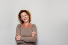 Smiling woman standing with arms crossed. Close up portrait of smiling woman standing with arms crossed against white wall Stock Image