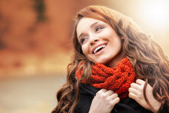 Smiling woman standing in autumn scenery. Smiling young woman standing in autumn scenery Royalty Free Stock Images