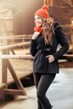 Smiling woman standing in autumn scenery. Smiling young woman standing in autumn scenery Stock Images