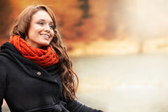 Smiling woman standing in autumn scenery. Smiling young woman standing in autumn scenery Royalty Free Stock Photo
