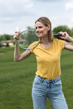 Smiling woman standing with badminton racquet and shuttlecock in park Stock Photography