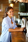 Smiling woman standing at the bar using mobile Stock Photos