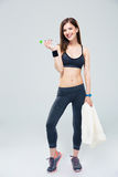 Smiling woman standing with bottle of water and towel Royalty Free Stock Photo