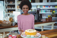 Smiling woman standing at counter in cafe Stock Images