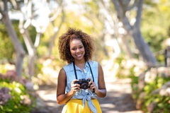 Smiling woman standing with digital camera Stock Photos