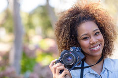 Smiling woman standing with digital camera Royalty Free Stock Photography