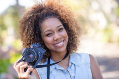 Smiling woman standing with digital camera Royalty Free Stock Photo